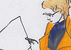 Woman in orange coat reading